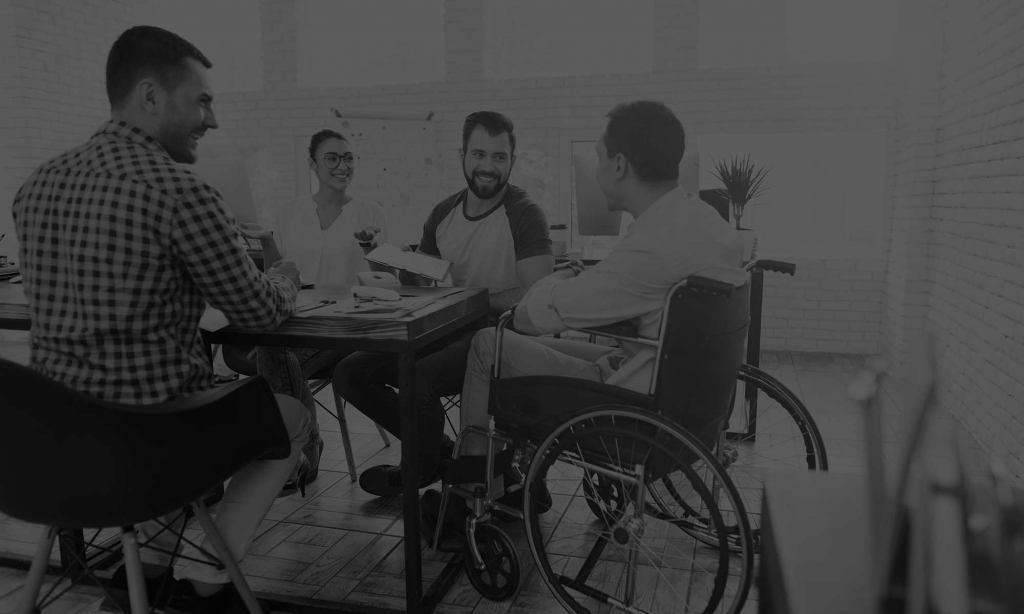 A meeting with a wheelchair user in an office environment. 4 people sit on chairs around a desk, at the top of the table is a wheelchair user.
