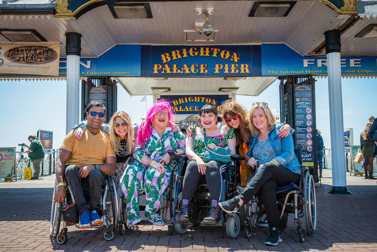 Group of 6 Enhance the UK trainers most of whom are wheelchair users posing together in front of Brighton Pier Sign