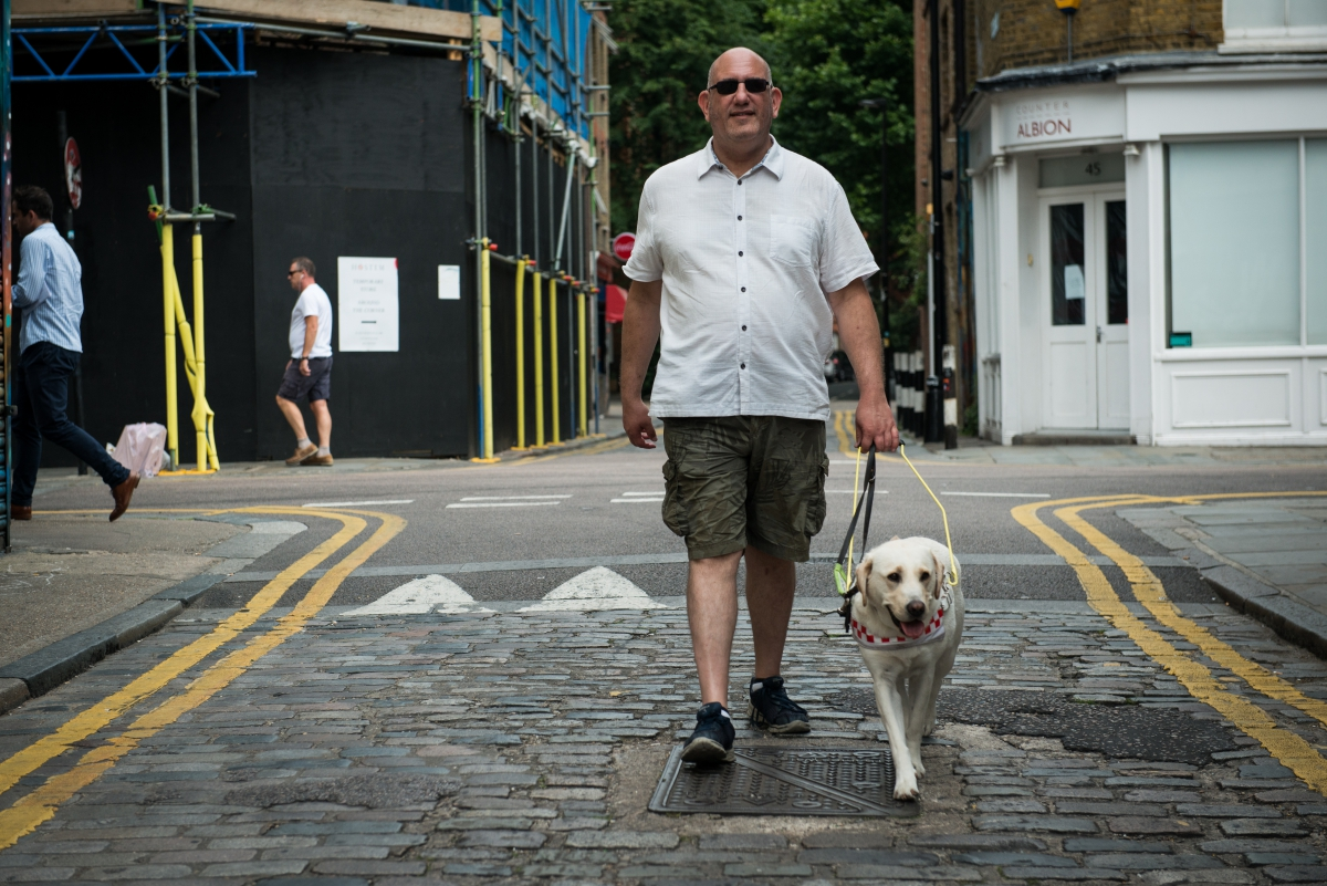 Visually impaired man walking down cobbled street with guide dog in harness