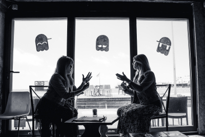 black and white photo of 2 ladies sat in a gaming cafe in front of a window signing
