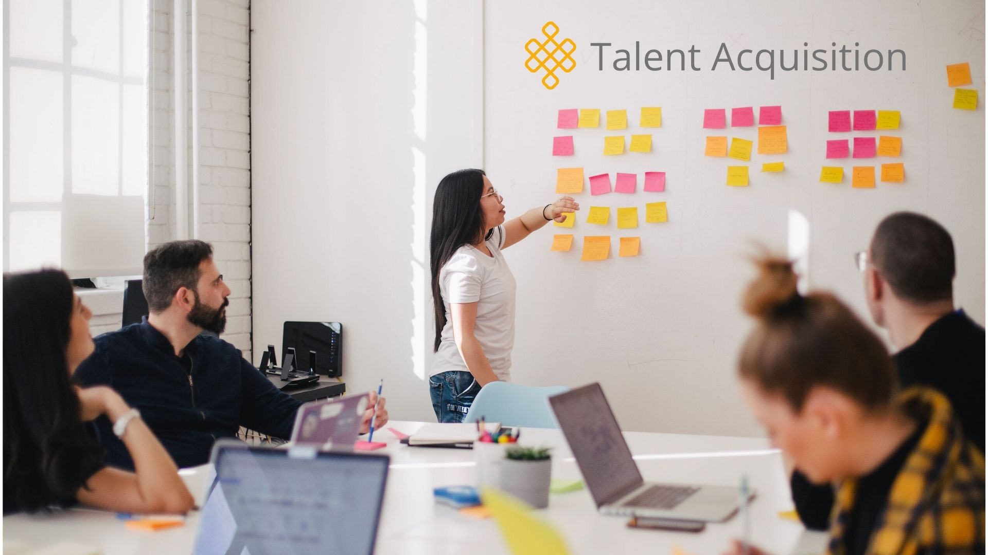 A team meeting with a woman standing in front of a white board entitled Talent Acquisition
