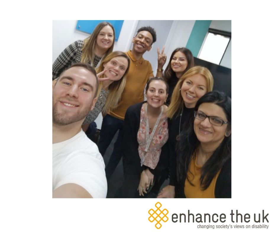 Jennie and Justin delivering disability awareness training to a staff team from Badenoch + Clark. Everyone is smiling at the camera in a selfie pose.