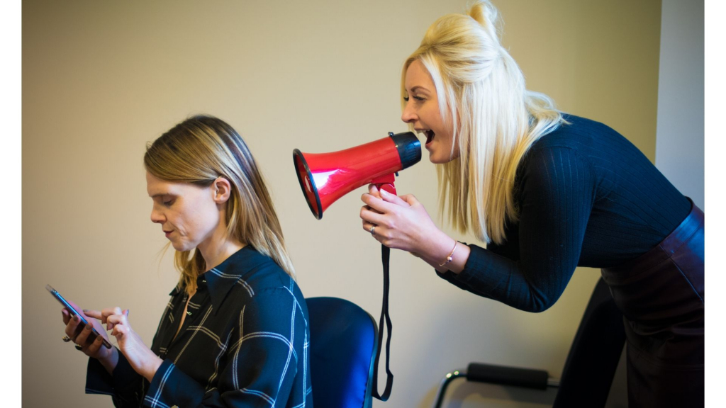 A deaf woman is sitting on a chair looking at her phone. Behind her stands another woman with a red megaphone shouting at the back of her head.