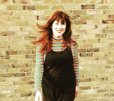 Claire Holland, deputy CEO of Enhance The UK. She is wearing a black dress with a striped multi-coloured top underneath.