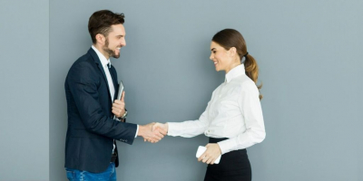 Learn how to communicate with Deaf and Hearing Impaired Colleagues. A man and woman in business clothes shake hands and smile at each other