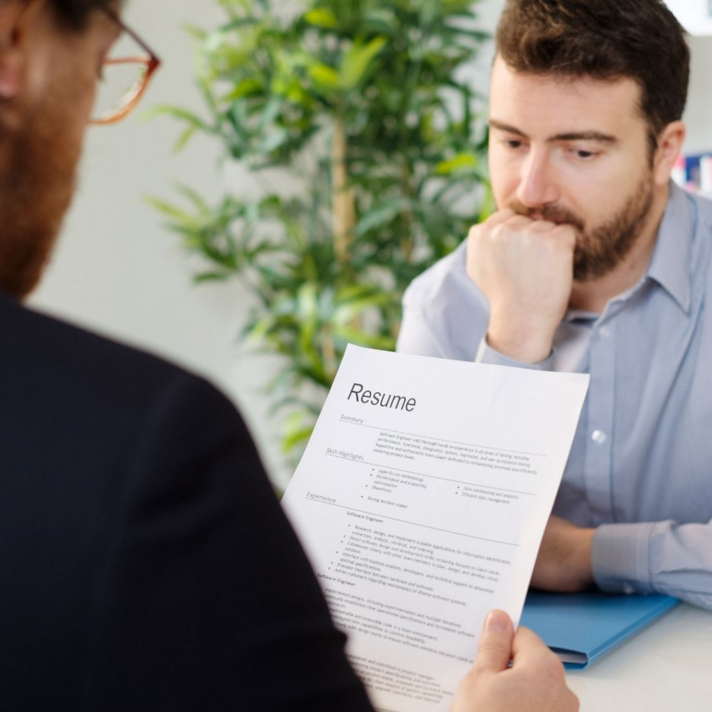 What is a hidden disability? A man in a job interview nervously bites his nails whilst the interviewer reads his CV