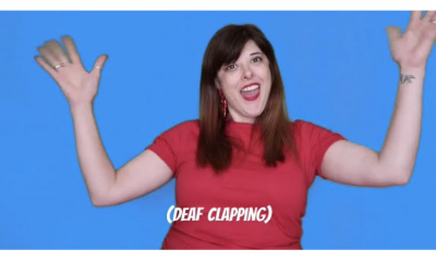 Free British Sign Language Lessons with Enhance The UK - Claire demonstrates the sign for deaf clapping by waving her hands in the air.