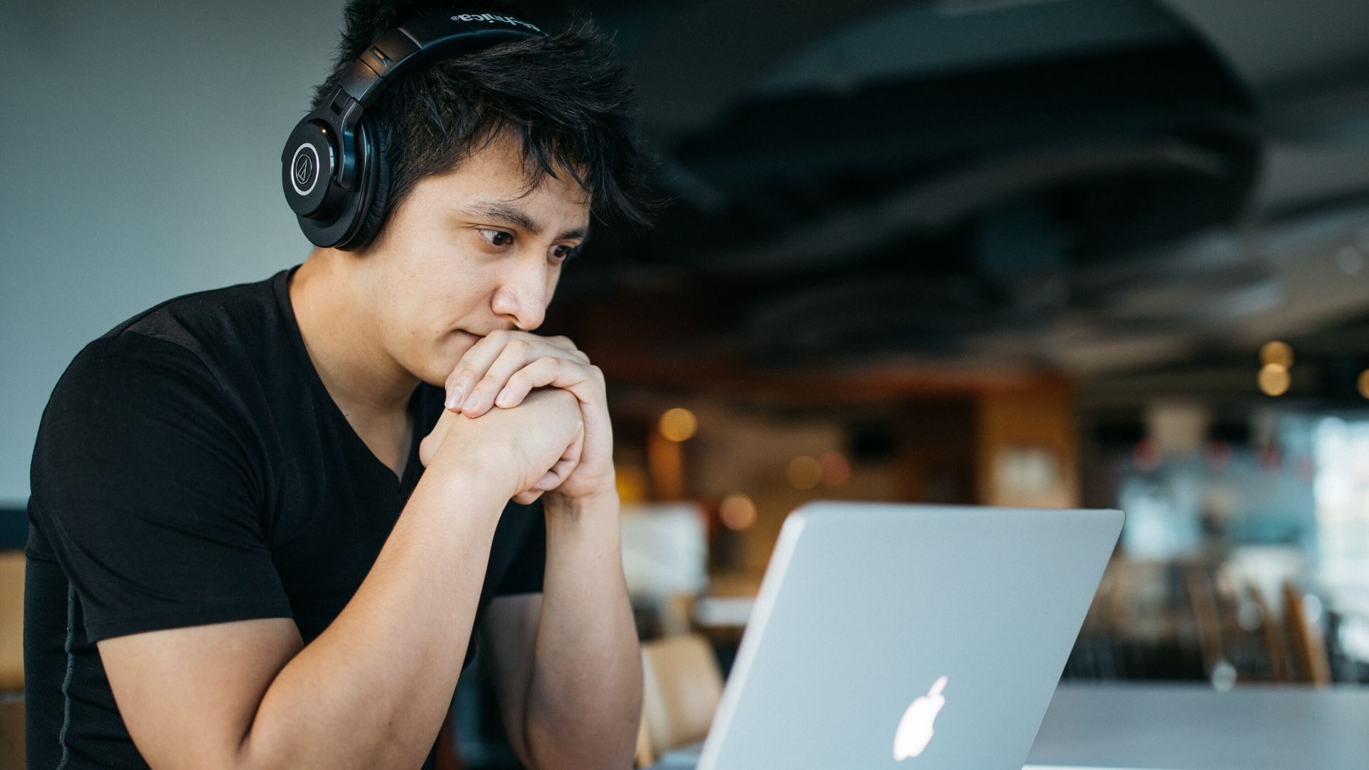 accessible video calls - a man sits in front of his laptop screen wearing headphones and a black tshirt, his hands are together with his chin resting on them