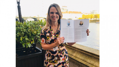 Jennie Williams CEO holds up the Power 100 List brochure whilst standing by the River Thames