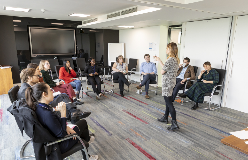 Jennie talking to a group of delegates facing them in a corporate environment