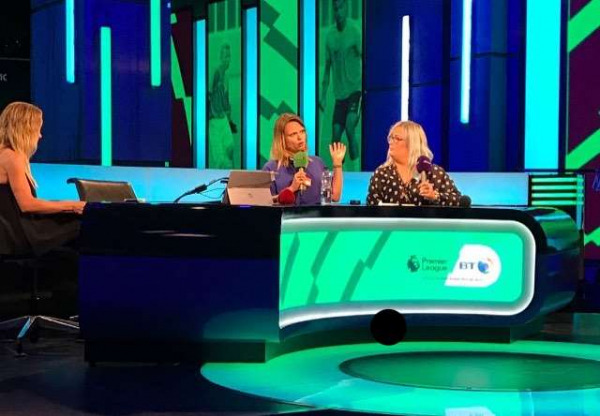 Jennie and Emily are sat the BT sport Premier League desk holding microphones with an unknown lady sat beside them.