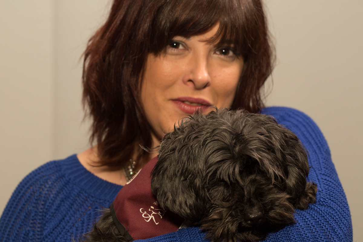 Claire Holland holding a small dog with a maroon hearing dog coat on