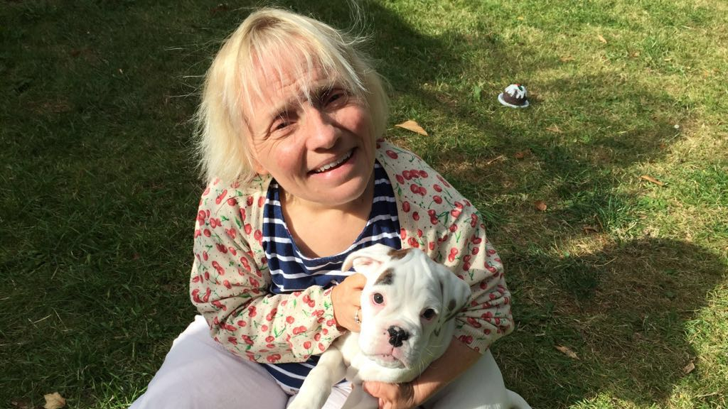 Trainer Becky Batten sitting on grass, holding a small white dog.