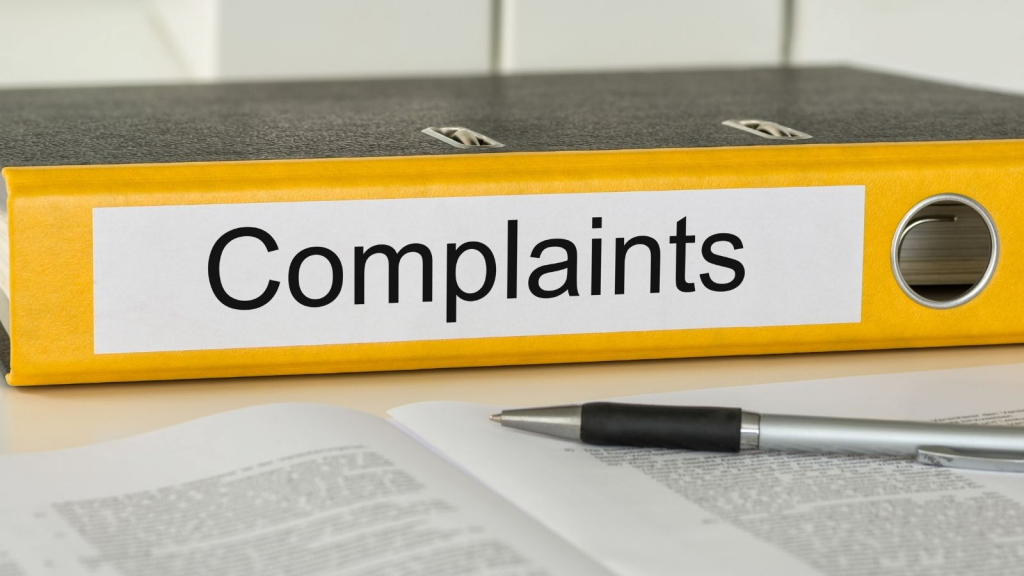 Accessible complaints procedure - a yellow ringbinder folder with the word complaints written on the side. On the desk beside it is paperwork and a pen