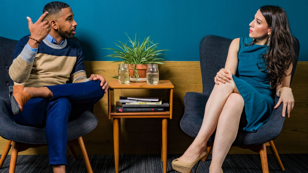 communication impairment - a smartly dressed man and woman sit opposite each other on comfortable chairs having a conversation. Both wear smart work clothes and make eye contact with each other